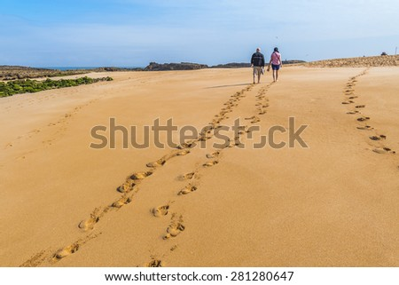 Tourists walking on beach in Oualidia, Atlantic coast of Morocco - stock photo