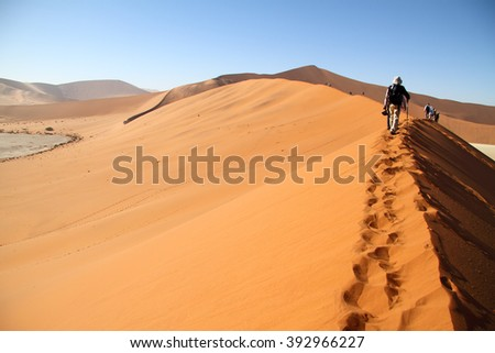 Tourists walking up a dune in Sossusvlei, Namib Naukluft National Park, Namib desert, Namibia. - stock photo