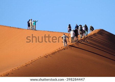 Tourists walking up a red dune in Sossuslvei, Namib Naukluft National Park, Namib desert, Namibia. - stock photo