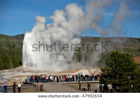 Tourists watching the Old Faithful erupting in Yellowstone National Park - stock photo