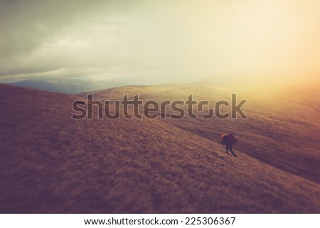 Tourists with backpacks climb to the top of the mountain in fog. Filtered image:cross processed vintage effect.  - stock photo
