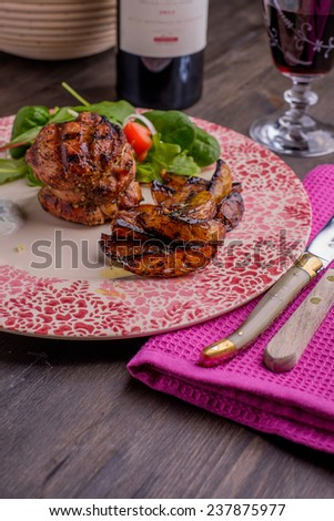 Tournedos with a salad on a wood table - stock photo