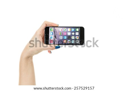 TOURS, FRANCE -?? February 6 2015: Female hand holding iPhone 6 Space gray variant isolated on white. iPhone 6 is a smartphone running iOS, developed by Apple Inc. - stock photo