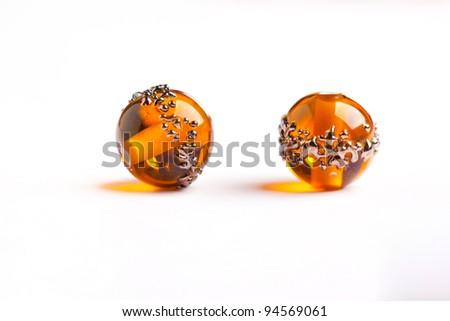 Tow orange glass beads closeup on white background - stock photo