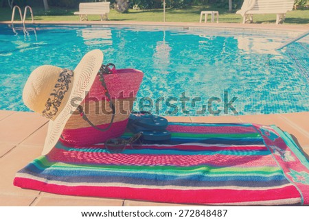 towel and bathing accessories by th side of  blue pool water, retro toned  - stock photo