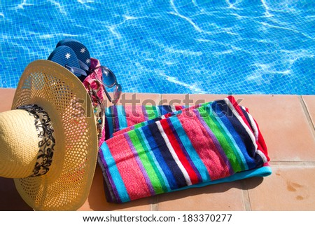 towel and bathing accessories near pool  side - stock photo