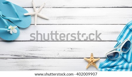 Towel and beach slippers on wood  ,summer background. - stock photo