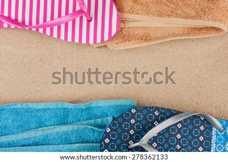 Towel and flip flops on the sand, with space for your text - stock photo