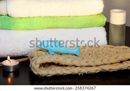 Towel pile with bast and dolphin form soap in the shower. - stock photo