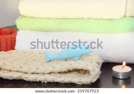 Towel pile with bast and dolphin form soap in the shower taken closeup. - stock photo