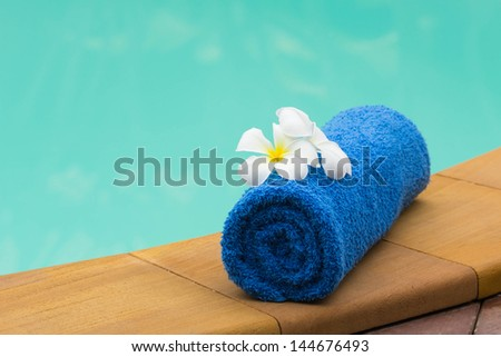 Towel set and flowers beside swimming pool - stock photo
