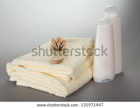 Towels, a wooden hairbrush and bottles with cosmetics on a gray background - stock photo