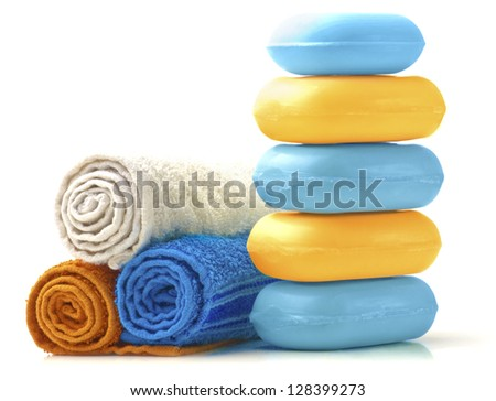 Towels and Stack of new colorful Soap Bars on white background. - stock photo