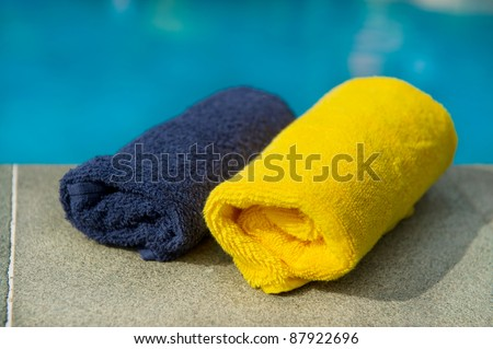 Towels in blue and yellow near the swimming pool - stock photo