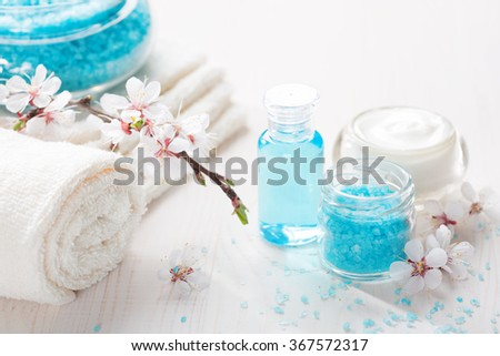 Towels , mineral bath salts, cream, shower gel, and flowers on the wooden table. Shallow DOF. Focus on the salt. - stock photo