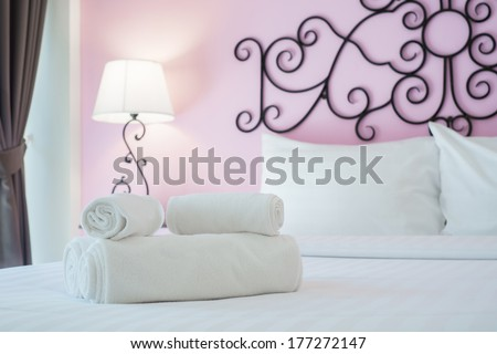 towels on bed with lamp in the corner of the room - stock photo