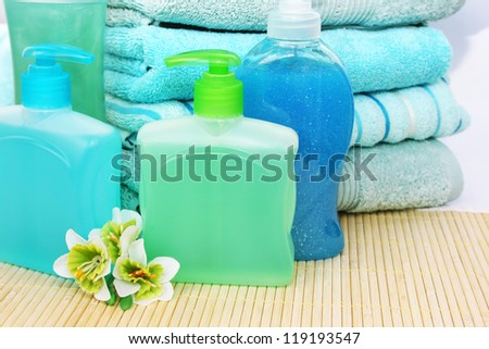Towels, soaps and shampoo on bamboo mat. - stock photo