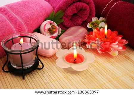 Towels, soaps, flowers and candles on mat background. - stock photo