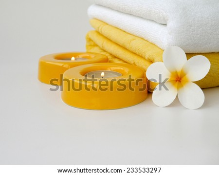 Towels, two candles and frangipani flower - stock photo