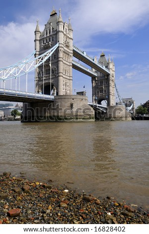 Tower Bridge at low tide over the River Thames, London, England, from the East, in summer, as the sun gets high in the sky - stock photo