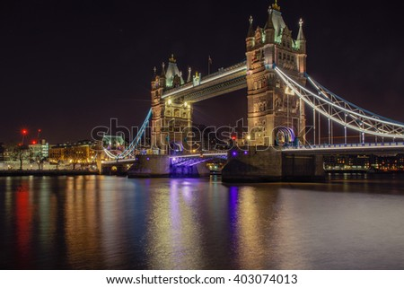 Tower Bridge in London, UK, illuminated at night time with reflection from Thames - stock photo