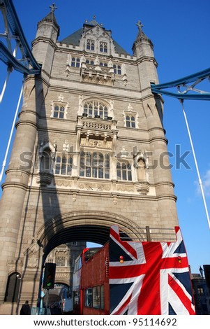 Tower Bridge with city bus covered flag of England, London, UK - stock photo