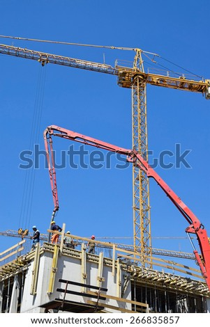 Tower crane is working at the construction of a new building - stock photo