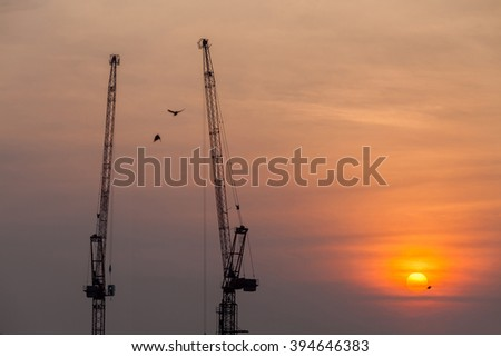 Tower crane on a construction site at sunset, Industrial construction cranes in silhouettes, Thailand - stock photo