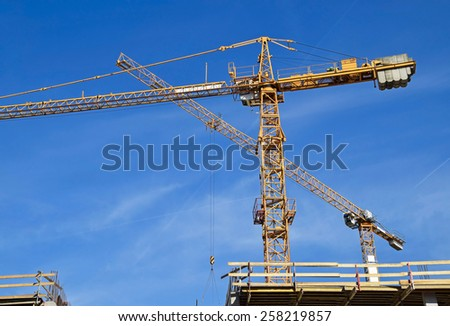 Tower cranes at the construction site - stock photo
