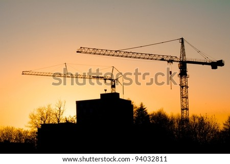 Tower cranes on a construction site behind buildings and trees, with a colorful sunset in Freiburg, Germany - stock photo