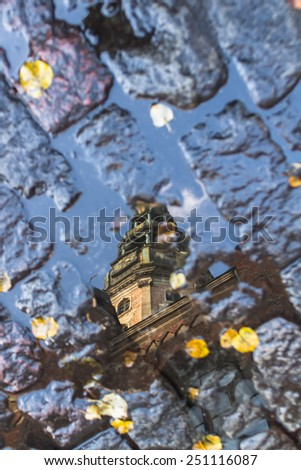 Tower of Catholic Duomo in the center of Riga, Latvia is reflected in a puddle in the fall, among fallen leaves and pavers - stock photo