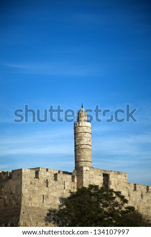Tower of David and part of the Jerusalem old city wall on the background of cloudy sky, with plenty of copy space. - stock photo