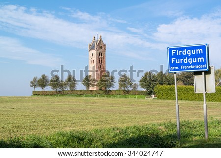 Tower of demolished church and town sign of Firdgum, small village in Friesland, Netherlands - stock photo