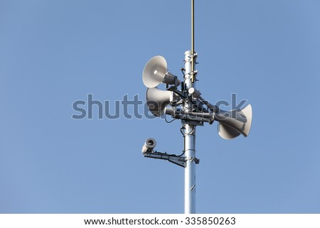 Tower of loudspeaker against clear blue sky - stock photo