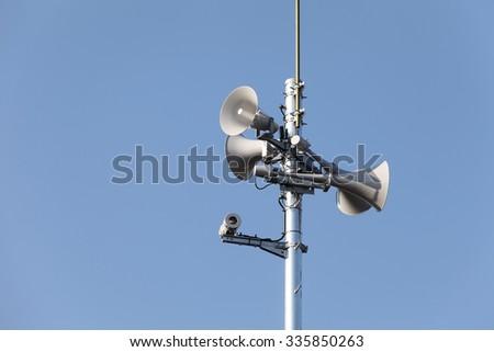 Tower of loudspeaker against clear blue sky - stock photo