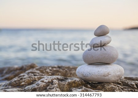 Tower of stones piles on top of a rock on a tranquil deserted beach at evening sunset - stock photo