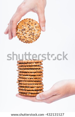 Tower of tasty cookies with sesame and flax seeds on women hand, one hand is taking the cookie isolated with white background  - stock photo