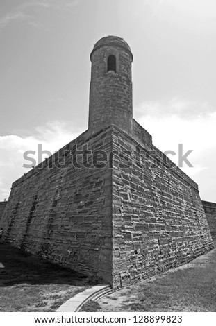 Tower, walls and field of the old Castillo de San Marcos, in St. Augustine, Florida, on a sunny and overcast day. Black and White. - stock photo