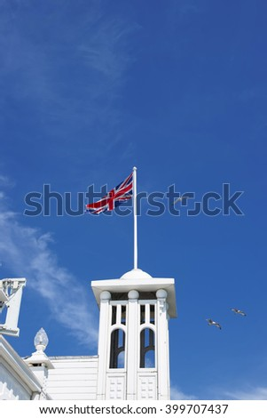 Tower with a UK flag in Brighton Pier in East Sussex in the UK. It is also called Brighton Marine Palace and Pier, or Palace Pier. It is under the protection of the UNESCO. - stock photo