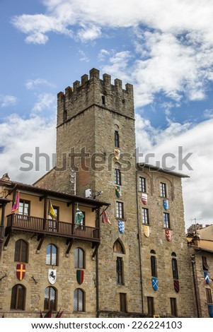 Tower with flags and shields at the Piazza Grande of Arezzo, Italy - stock photo