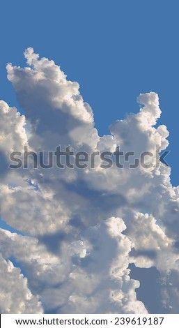 Towering cumulus clouds against a beautiful blue sky. - stock photo