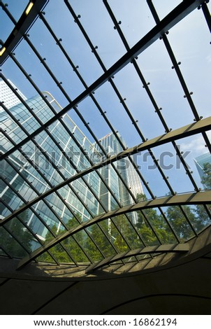 towering office blocks seen through glass atrium, London Docklands, against clear blue sky - stock photo