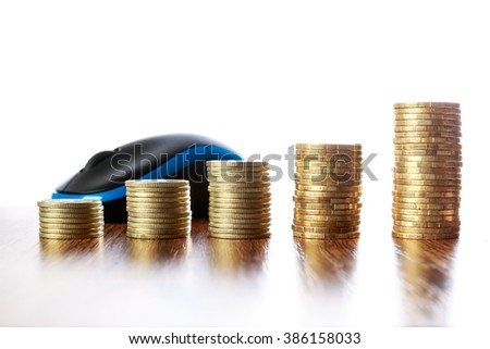 Towers of coins on wooden table in front of computer mouse - stock photo