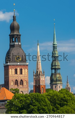 Towers of Riga seen in Riga. Three church towers in the picture are the Riga Dome cathedral,  St. Saviour's Church and St. Peter's church. On the right is Building of Academy of Sciences - stock photo