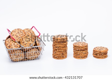 Towers of tasty cookies and shopping basket full of cookies with sesame and flax seeds isolated with white background  - stock photo