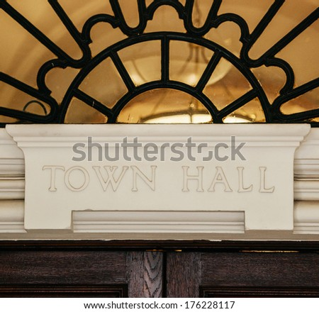 Town Hall sign carved in stone above a wooden door. - stock photo