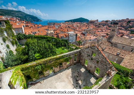 Town of Dubrovnik with old foliage covered house in the foreground. - stock photo