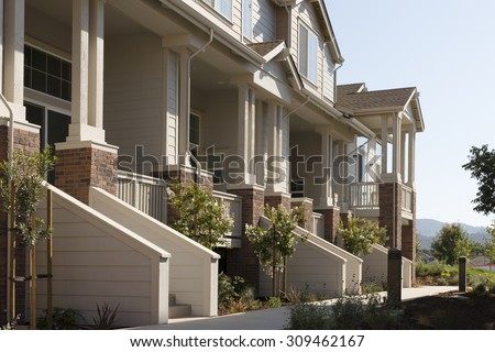 Townhome porches along a common walkway. - stock photo
