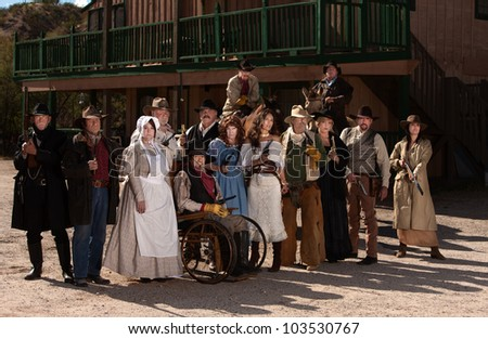 Townspeople posing outside in an American old west scene - stock photo