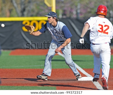 TOWSON, MD - MARCH 29: Gilman player Ryan Ripken (l) takes a throw at first base in a game against Calvert Hall March 29, 2012 in Towson, MD. Ripken is the son of Cal Ripken Jr. - stock photo